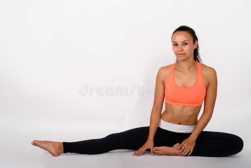 Full body shot of young Asian woman stretching her right leg whi royalty free stock photography
