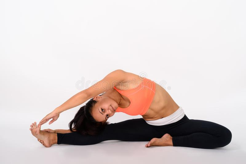 Full body shot of young Asian woman stretching to the side while stock photography