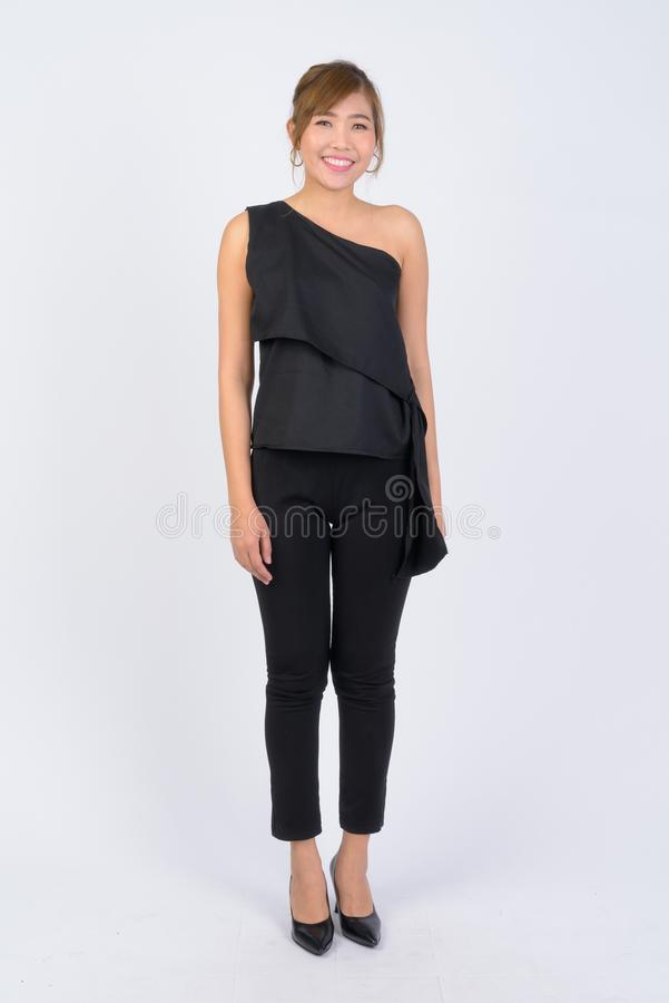 Full body shot of young happy Asian businesswoman smiling stock photography