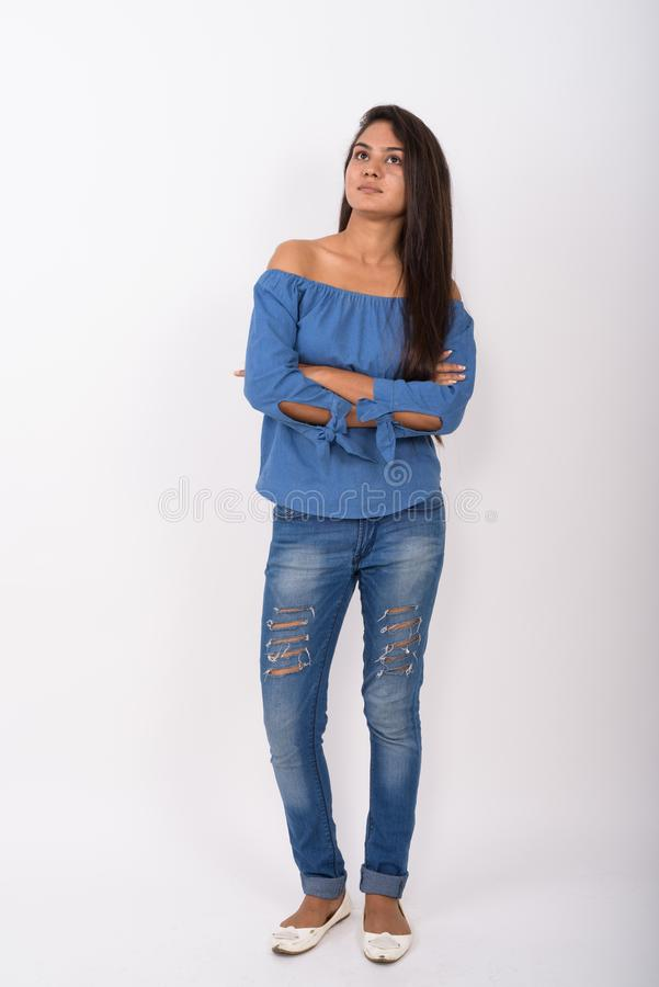 Full body shot of young Indian woman standing while thinking wit stock images