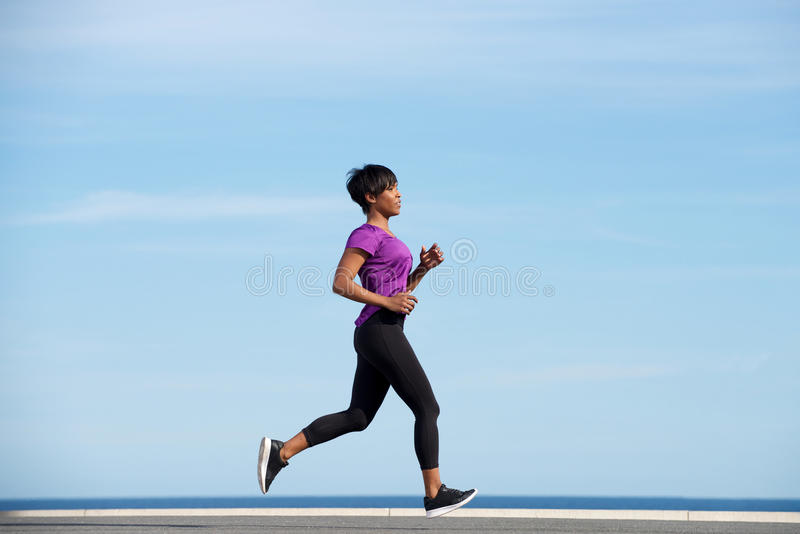 Full body side fit young african woman running outdoors against blue sky stock photography