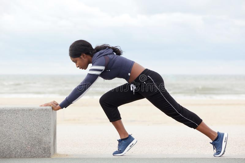 Side portrait of fit young african american woman stretching muscles at the beach royalty free stock images