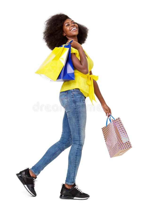Full body side portrait of young black woman walking with shopping bags stock images