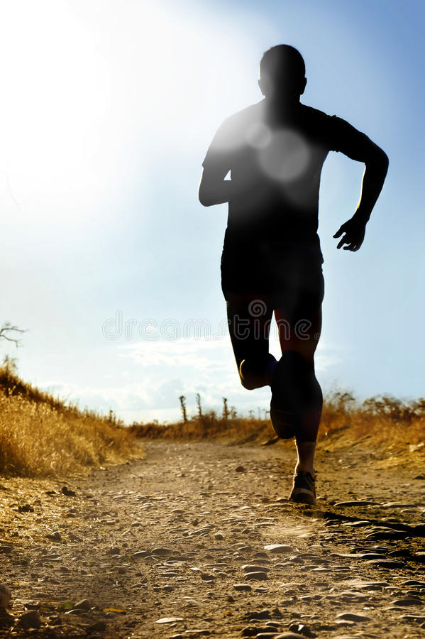 Full body silhouette of extreme cross country man running on rural track jogging at sunset. Full body silhouette of extreme cross country man running and royalty free stock photos
