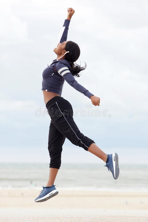 Full body sporty african american woman jumping with hand raised at the beach royalty free stock images