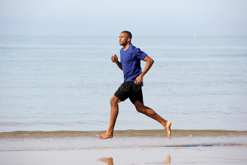 Full body young african male running along sea shore royalty free stock images