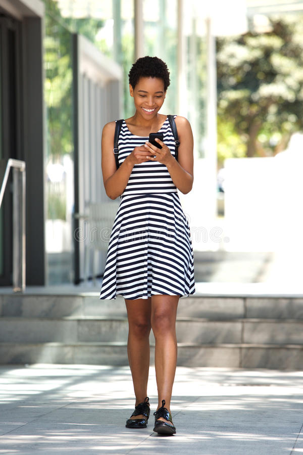 Full body young woman walking with cell phone in the city stock photography