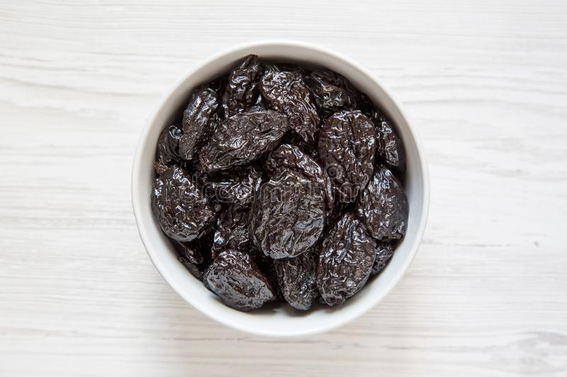 Full bowl of dry prunes on a white wooden surface, top view. Overhead, flat lay, from above royalty free stock images