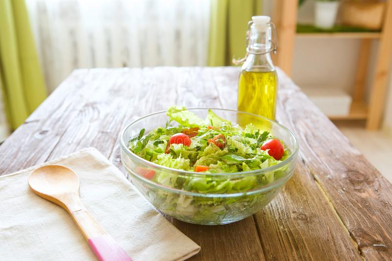 Full bowl of fresh green salad on a wooden table against on a rustic kitchen. Concept healthy lifestyle and simple food royalty free stock photos