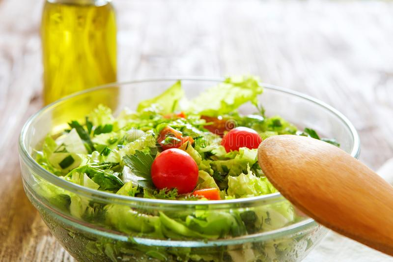 Full bowl of fresh green salad on a wooden table against on a ru stock images