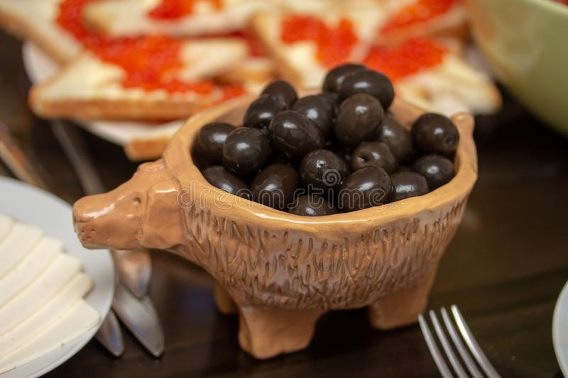 Full bowl of gorgeous black olives. In this handmade bowl, gorgeous black olives look very appetizing royalty free stock images