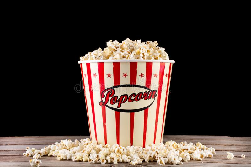Full box with popcorn and spilled on retro wooden desk. Big classic full box with popcorn and spilled on retro wooden desk and black background. Movie and cinema royalty free stock image