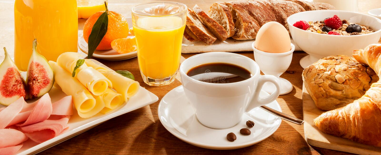 Full breakfast on table. Full breakfast with figs, egg, meat, bread, coffee and juice stock image
