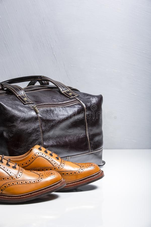 Full Broggued Oxford Calf Leather Shoes Along With Dark Brown Leather Travel Bag. Male Tanned Full Broggued Oxford Calf Leather Shoes Along With Dakr Brown stock photos