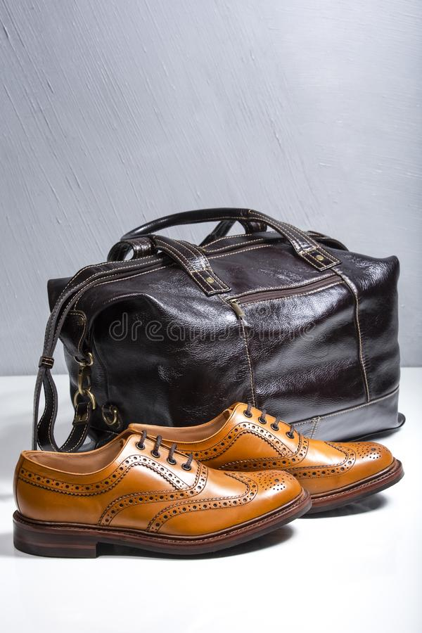 Full Broggued Oxford Calf Leather Shoes Along With Darr Brown Leather Travel Bag. Male Tanned Full Broggued Oxford Calf Leather Shoes Along With Darr Brown royalty free stock photos