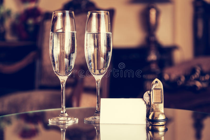 Full champagne glasses, antique keys and blank white card. Luxury hotel apartment. Room service concept. Vintage, retro stock image