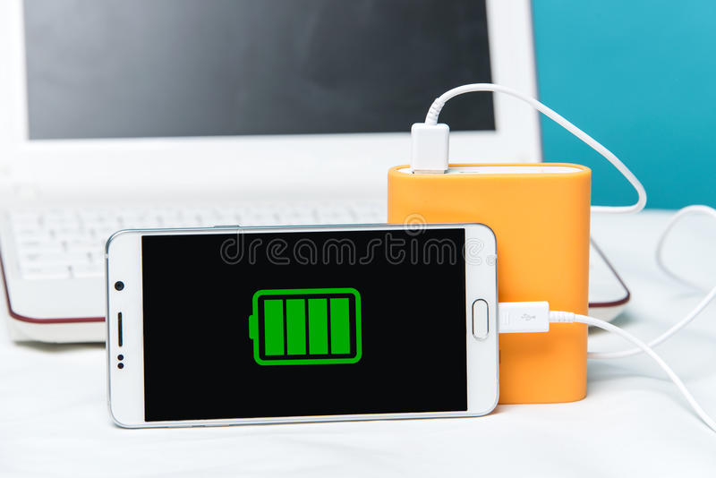 Full charge of a smartphone on its monitor with the cable connected to the special power bank. stock photo