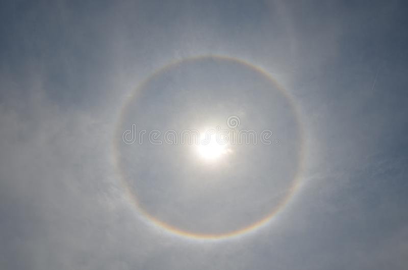 Full circle rainbow around Sun at noon, rays catch the thin vapour formed of ice crystals stock photo