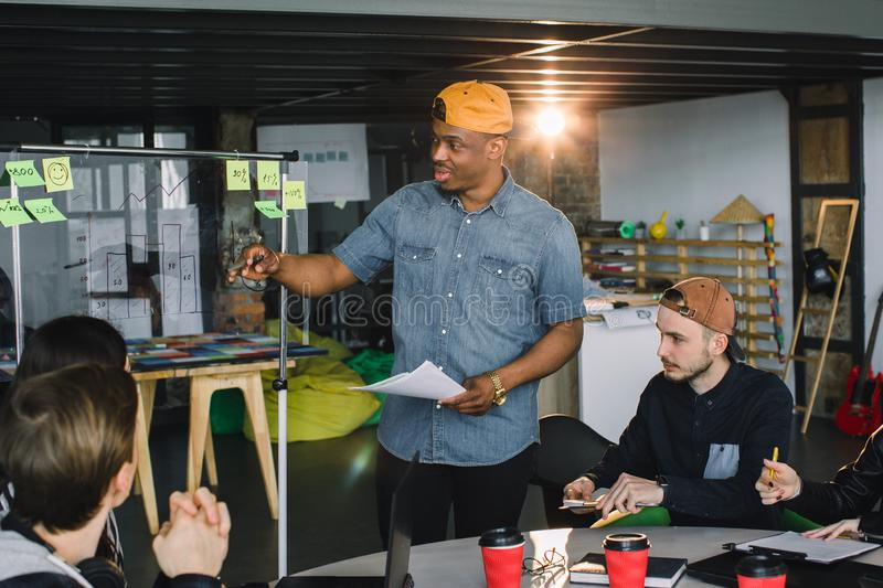 Full concentration at work. Corporate team working colleagues working in modern office. African man making presentation royalty free stock photography