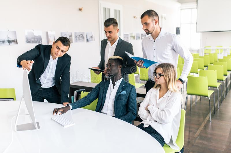 Full concentration at work. Group of young business people working and communicating while sitting at the office desk together. Group of young business people royalty free stock photography