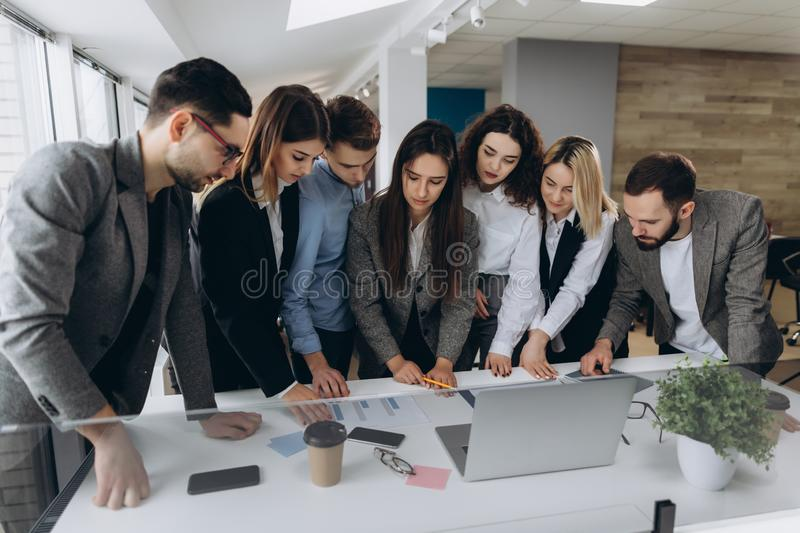 Full concentration at work. Group of young business people working and communicating while standing in modern office royalty free stock photo