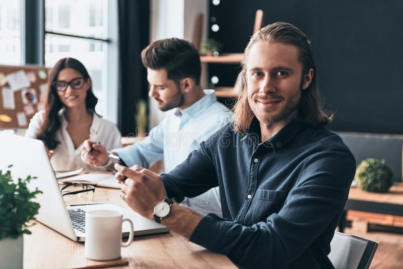Full concentration at work. Young modern colleagues in smart casual wear working while spending time in the office royalty free stock photos