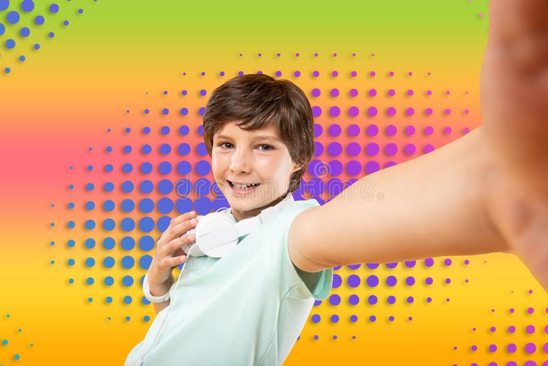 Merry joyful boy grinning on colorful background stock photos