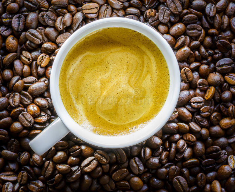 Full cup of Coffee. Cup of Coffee on and with Coffee Beans royalty free stock photo