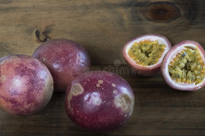 Full and cut in half passion fruits against a wooden background stock photos