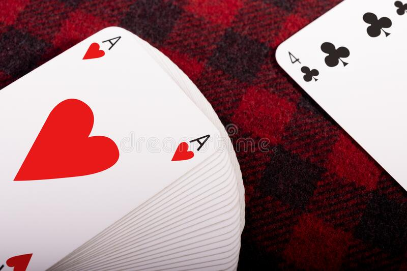 Full deck of playing cards. With ace of hearts on top and card club 4 lying on checkered plaid. Horizontal photo. Place for text royalty free stock photography