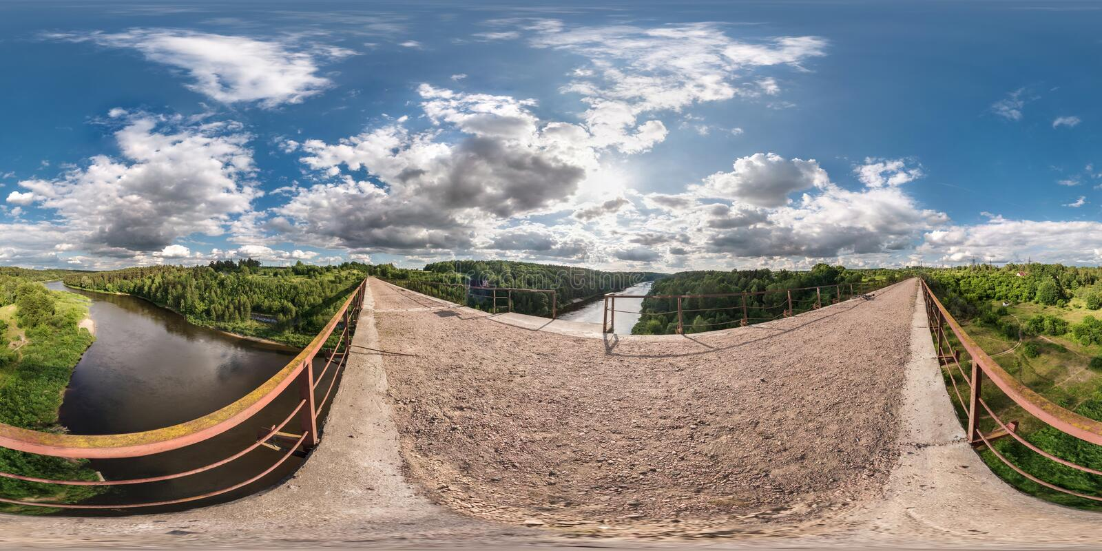 Full 360 degree seamless panorama in equirectangular spherical equidistant projection. Panorama view on abandon bridge near river. With nice clouds. Skybox as stock photography