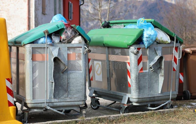 full dumpster två och många avskrädepåsar på gatan arkivfoton