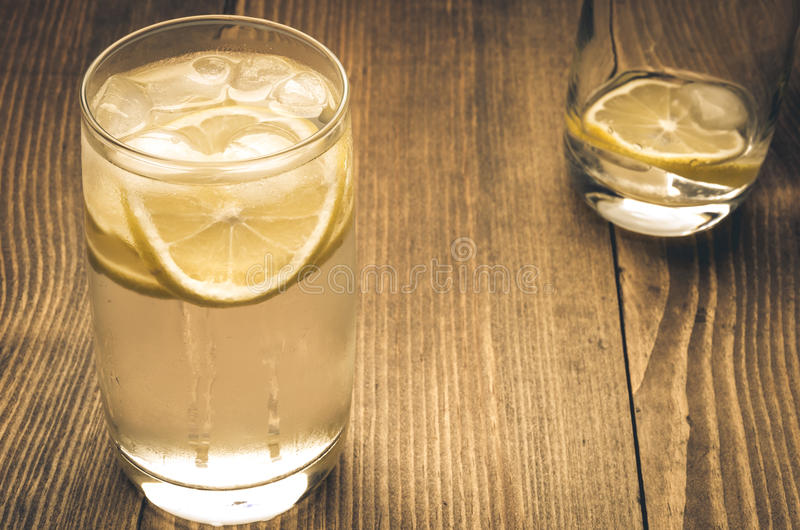 Full and empty drink. Full and empty glass with ice and a lemon stock images