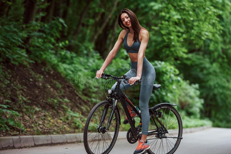 Full of energy. Female cyclist on a bike on asphalt road in the forest at daytime stock photography