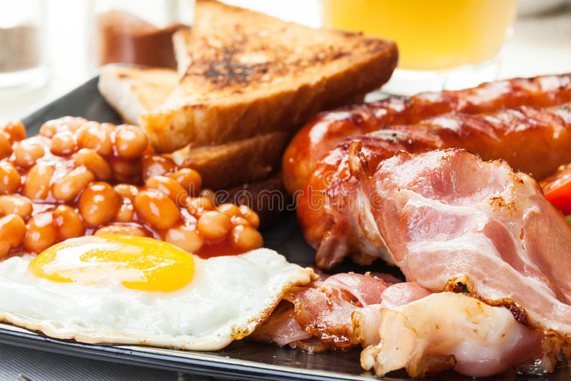 Full English breakfast with bacon, sausage, egg, baked beans and orange juice. Full English breakfast with bacon, sausage, fried egg, baked beans and orange stock image