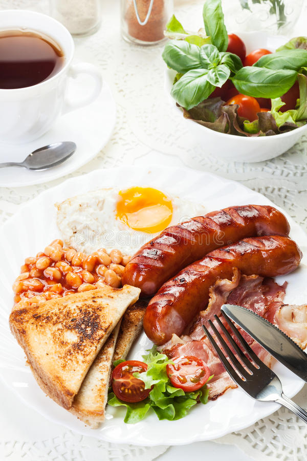 Full English breakfast with bacon, sausage, fried egg and baked beans. Full English breakfast with bacon, sausage, fried egg, baked beans and tea royalty free stock image