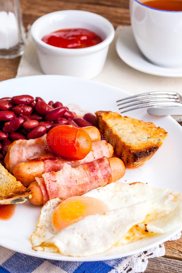 Full english breakfast. Full English breakfast with bacon, sausage, fried egg, baked beans and tea royalty free stock photography