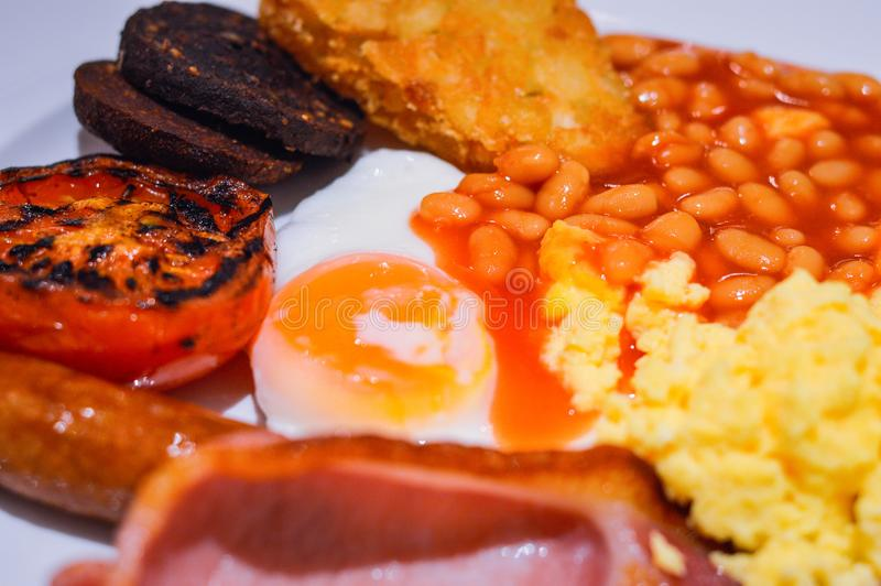 Full English Breakfast with Bacon, Sausage, Fried Egg, Beans, Scrambled Eggs, Hash Browns and Black Pudding. stock image