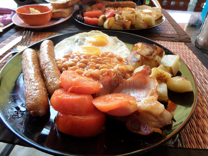 Full English Breakfast. A big plateful of full English breakfast. Sausages, eggs, bacon, saute potatoes tomatoes, beans and toast. Photograph from Udon Thani royalty free stock photos