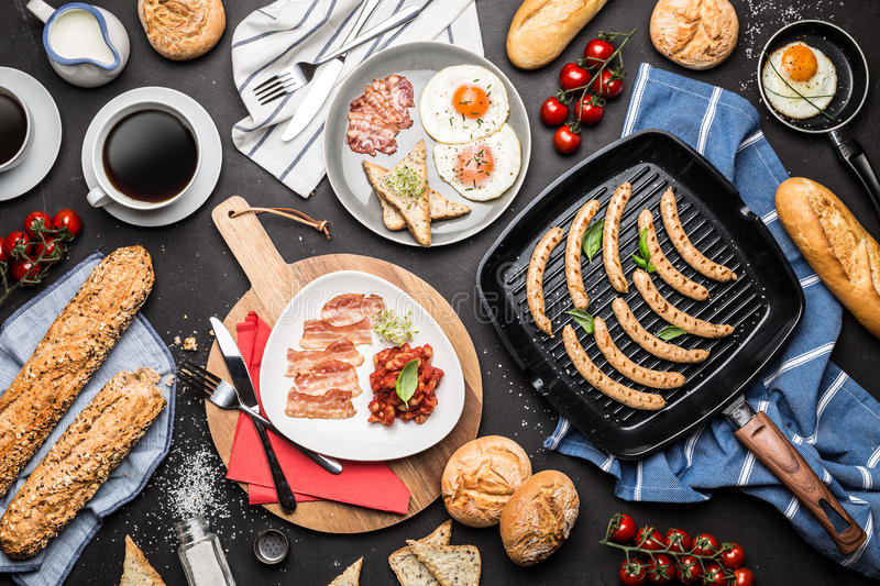 Full english breakfast on black chalkboard background. Captured from above top view, flat lay. Coffee, fried eggs, baked beans, sausages, bread rolls, toast and royalty free stock photo