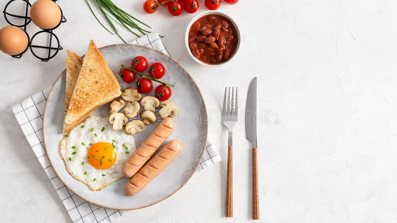 Full English Breakfast including sausages, grilled tomatoes and mushrooms, egg, baked beans and bread. Top view, copy space stock photos