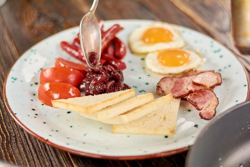 Full english breakfast on plate. Chef putting beans on plate with english breakfast. English breakfast in restaurant stock images