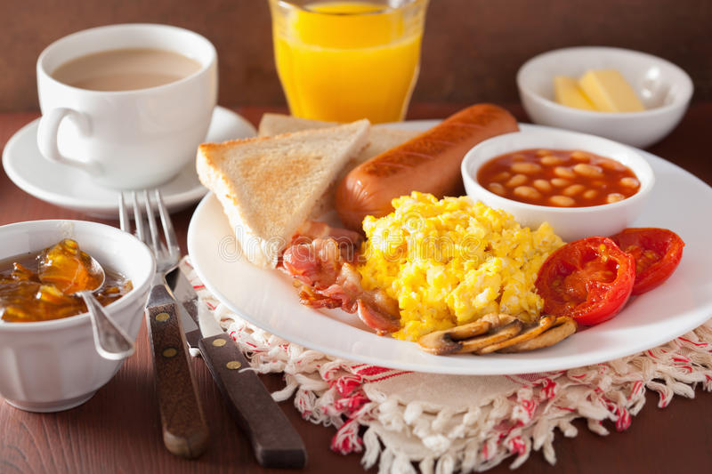 Full english breakfast with scrambled eggs, bacon, sausage, bean stock photos