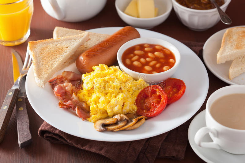 Full english breakfast with scrambled eggs, bacon, sausage, bean royalty free stock photography