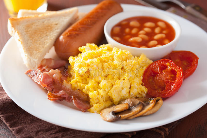 Full english breakfast with scrambled eggs, bacon, sausage, bean royalty free stock images