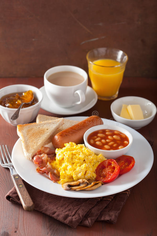 Full english breakfast with scrambled eggs, bacon, sausage, bean stock images