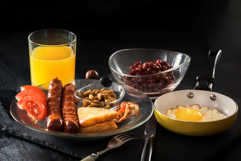 Full English breakfast with scrambled eggs in a frying pan, bacon, sausage, beans, tomatoes and juice royalty free stock images