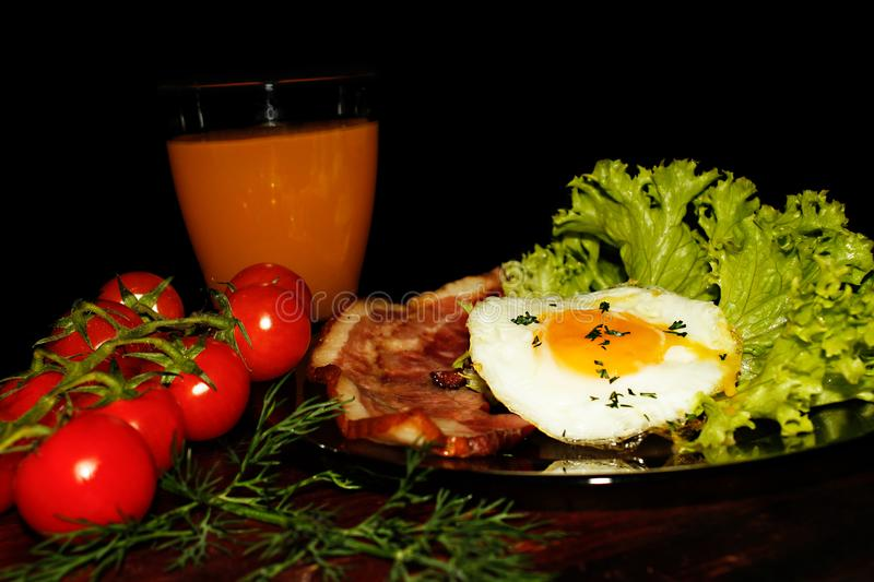 Full English breakfast with scrambled eggs, bacon, beans, tomatoes and orange juice. Black background. stock photo