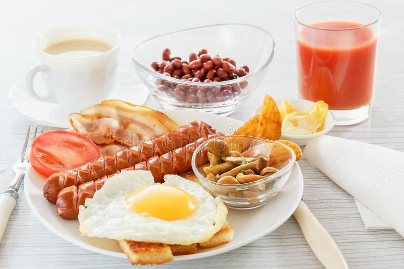 Full English breakfast with smoked sausages, fried egg, bacon, tomato, toast and beans. Tea with milk. A glass of fresh juice. Cutlery. Breakfast on a white royalty free stock photography