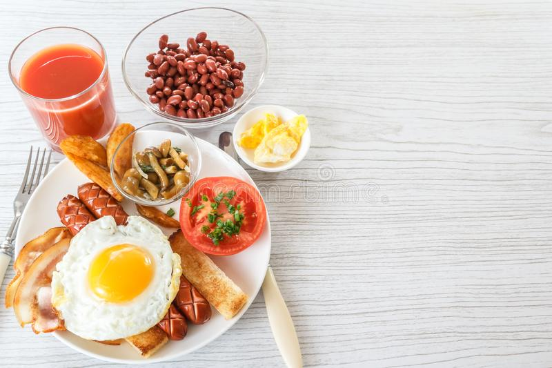 Full English breakfast with smoked sausages, scrambled eggs, bacon, tomatoes, mushrooms, toast and beans. A glass of fresh juice. royalty free stock images